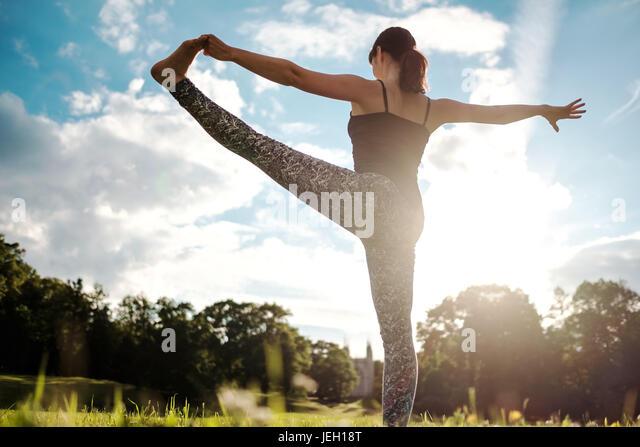 Caucasian woman in yoga standing balance Utthita Hasta Padangusthasana pose. Back view - Stock Image