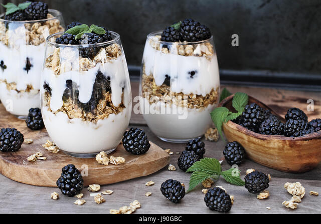 Blackberry parfaits made with Greek yogurt, granola and fresh blackberries. Extreme shallow depth of field with - Stock Image