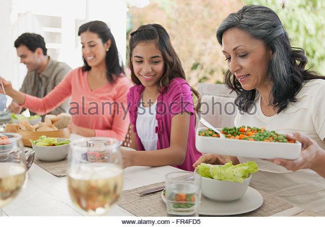 Hispanic Family Sitting Down To Dinner