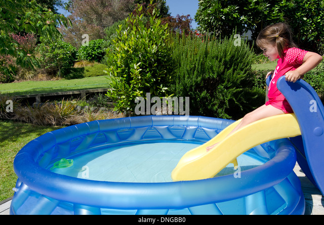 child girl slides on a slide into cool waters in a children inflatable pool - Inflatable Pool Slide