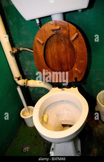 Old fashioned toilet with wooden seat with help scribbled in bowl