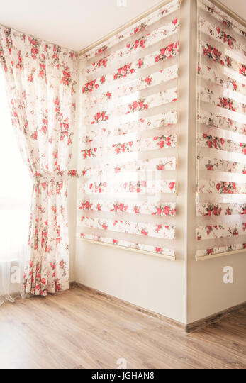 warm light through sheer white tulle and vintage floral curtains blinds with red roses in