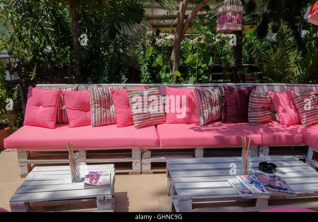 Outdoor Pink Patio Seating Area With White Wooden Table   Stock Image