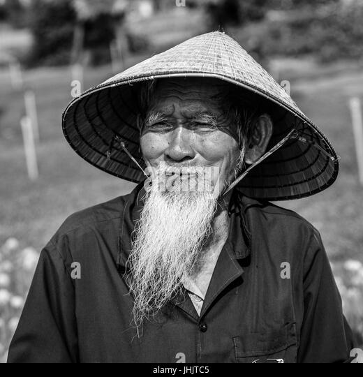 Bearded old man of vietnam in a conical hat black and white stock image