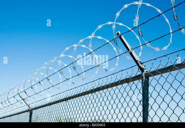 razor wire barbed wire and chain link combine to create a security fence