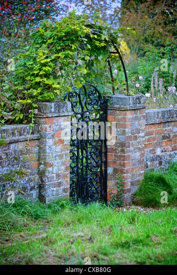 Charming Garden Gate And Arch With Old Red Brick Wall And Green Vine, Red Berries And