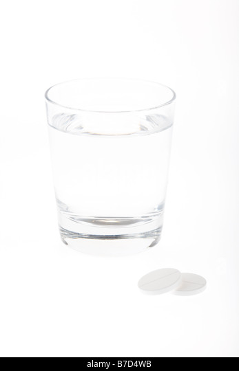 glass half full empty with water with two large soluble paracetamol ...