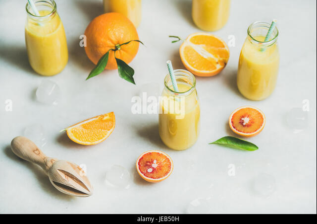 Healthy yellow smoothie with citrus fruit, marble background - Stock Image