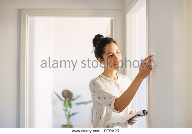 Young woman adjusting central heating control at home - Stock Image