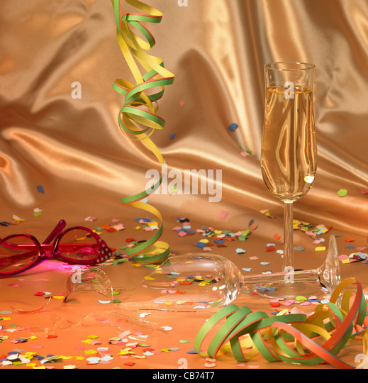 carnival background with a filled and a broken champagne glass in floating satin back with streamers and confetti - Stock Image