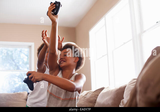 Two Brothers Playfighting Over Game Controllers In Living Room