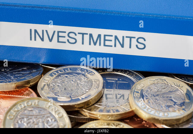 Investments portfolio on English pounds sterling money new pound coins GBP cash to illustrate investing and saving - Stock Image