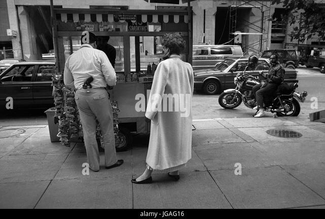 Policeman with gun in his trouser belt buys food at a food stand in central Washington DC, USA, 1988. - Stock Image