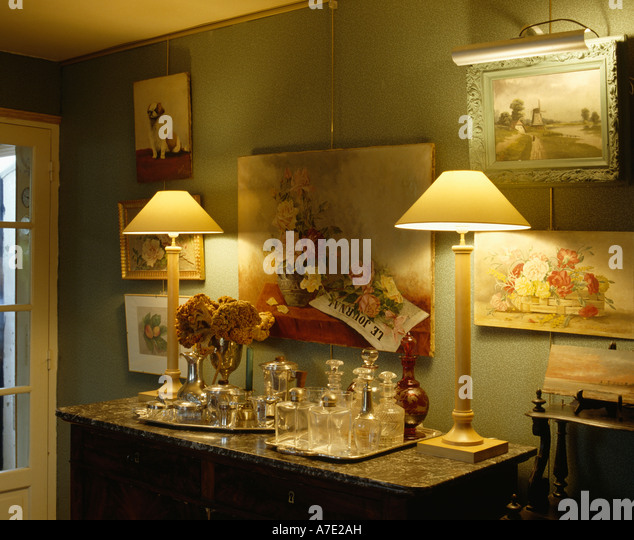 Lighted Lamps And Glass Decanters On Console Table Below Pictures On Green  Wall   Stock Image