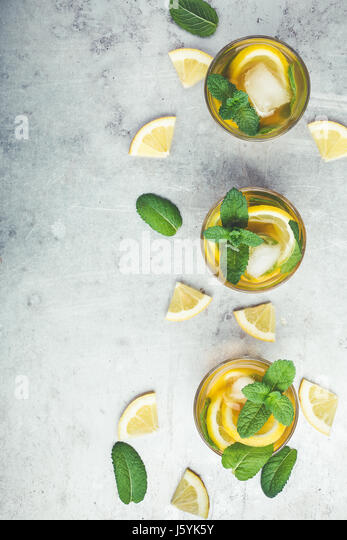 Homemade iced lemon sweet tea with mint on light gray table with copy space viewed from above, delicious refreshment - Stock Image