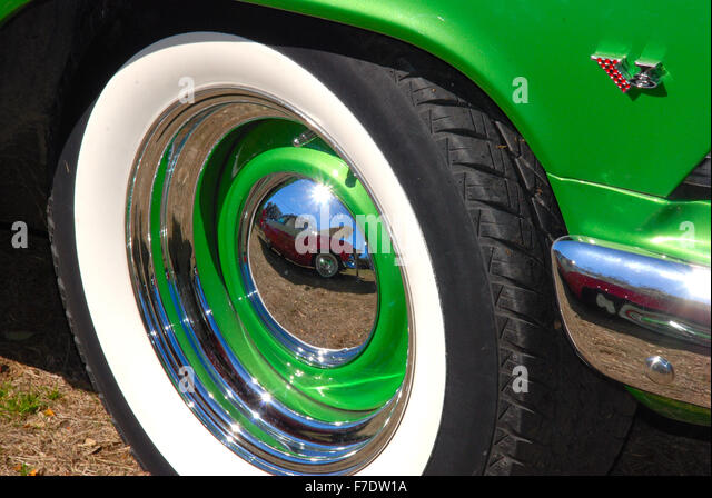 close up of a tire and hubcap on a classic car with green fender