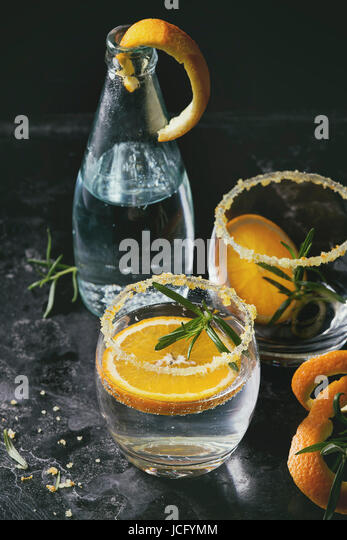 Tonic water cocktail with rosemary and orange. Two glasses and bottle with zest sugar and bubbles over black texture - Stock Image