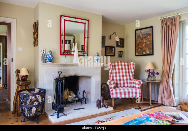 gingham wingback chair in sitting room with stone fireplace and murano glass mirror stock image