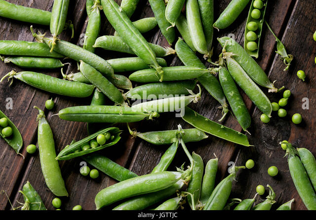 Young organic green pea pods and peas over old dark wooden planks background. Top view with space. Harvest, healthy - Stock Image