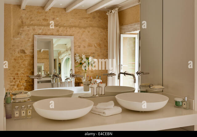 Twin Spoon CER 700 Basins By Agape In Bathroom With Rough Stone Walls    Stock Image