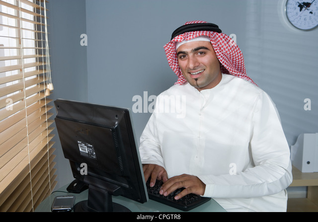 arab-man-in-front-of-a-computer-smiling-