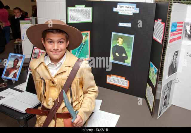 student age 12 costumed as jim bowie holding his namesake knife by his diorama at horace