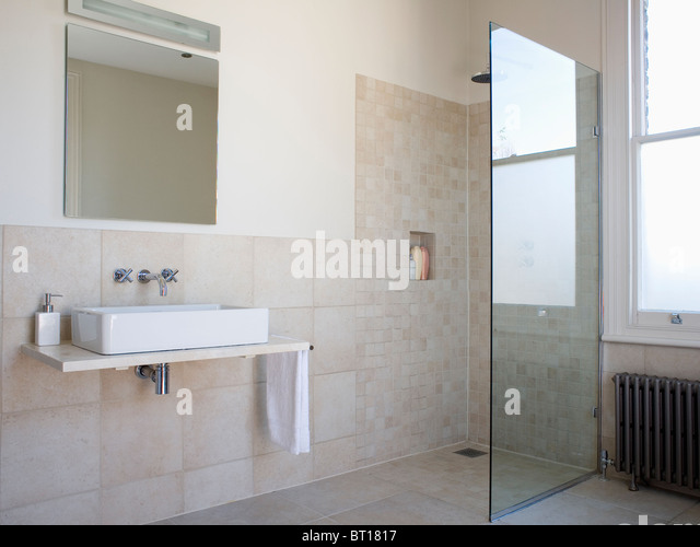 Walk-in wet room with glass shower wall in modern beige tiled bathroom with  large