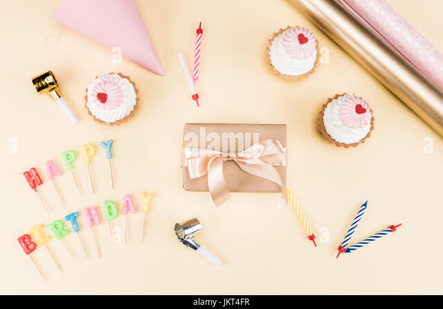 Top view of happy birthday lettering, envelope with ribbon, cakes and colorful cards on pink, birthday party concept - Stock Image