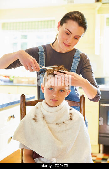 Portrait Unhappy Boy Getting Haircut From Mother In Kitchen