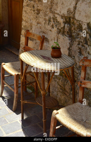 Rattan chairs and table against a crumbling old wall outside a cafe in  Chania  Crete. Rattan Chairs Stock Photos   Rattan Chairs Stock Images   Alamy