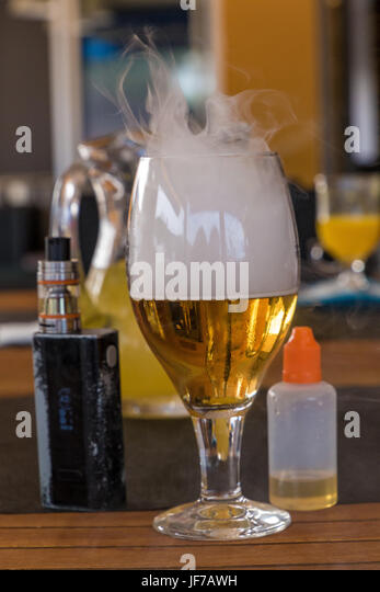 Vaporizer and smoking beer with bottle on table - Stock Image