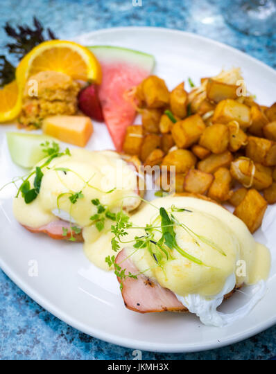 Classic Eggs Benedict (soft poached eggs, Canadian back bacon, and Hollandaise sauce on an English muffin), fried - Stock Image