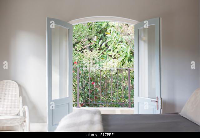 french doors open to balcony in luxury bedroom stock image