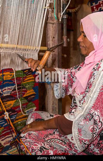 Berber Woman Weaving A Rug In Her Home. Ait Benhaddou Ksar, A