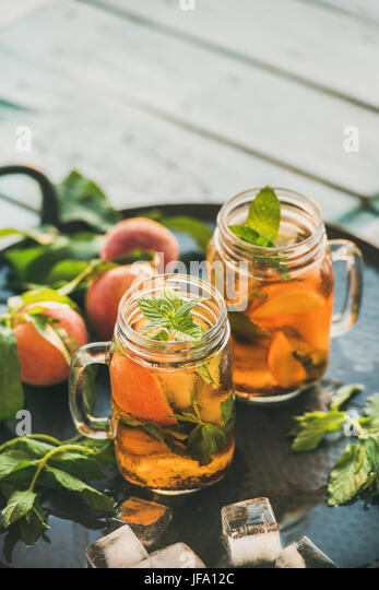 Summer refreshing cold peach ice tea on table, copy space - Stock Image