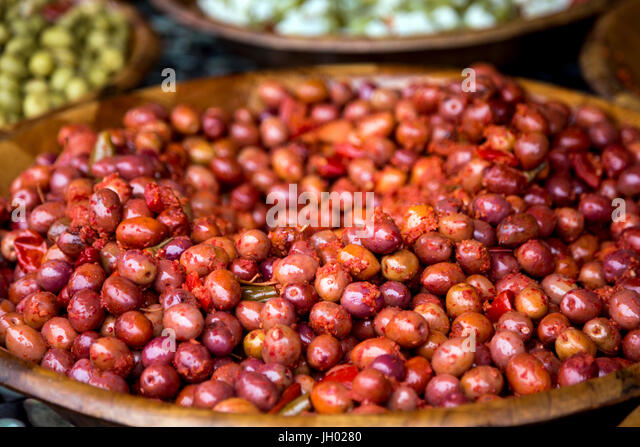 Red olives on a large wooden plate at Marché de Wazemmes (Wazemmes Market), Lille, France - Stock Image