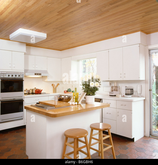 White Kitchen With Wooden Worktops indian asian woman in a stylish modern kitchen with white units