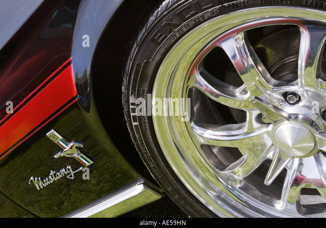 front wheel and side of a black ford mustang classic car with red racing stripe