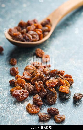 Sweet dried raisins on old kitchen table. - Stock Image