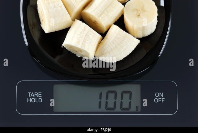peeled sliced banana in a black plate on digital scale displaying 100 gram stock