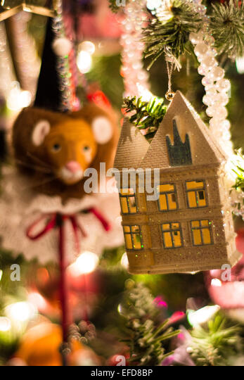 colorful christmas ornaments on a lighted christmas tree depict a sparkly white house with lighted windows - Lighted Christmas Ornaments