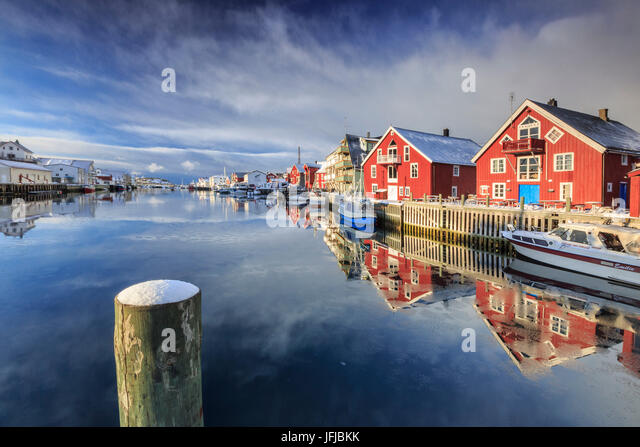 Red houses reflected in the canal of Henningsvaer, Lofoten Islands, Norway, Europe - Stock Image