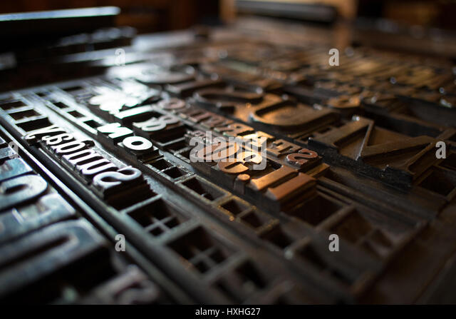 typeset letters and numbers are laid out on a vintage printing press stock image