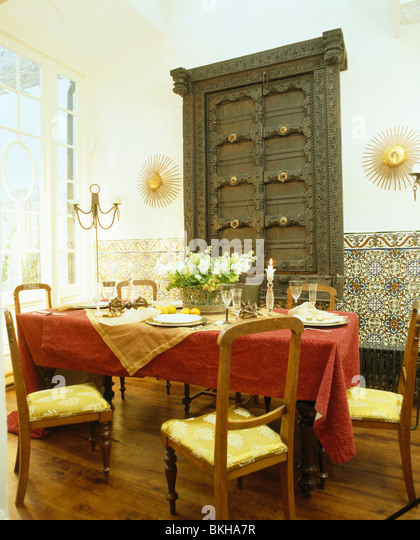 Carved Doors On Wall Cupboard In Spanish Dining Room With Red Cloth Table And Yellow