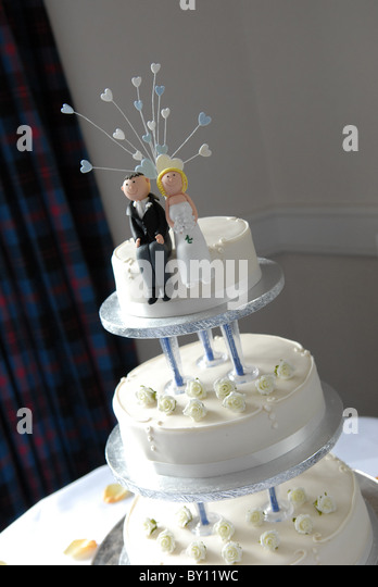 General View Of A White Round Three Tier Wedding Cake With Caricature Bride And Groom