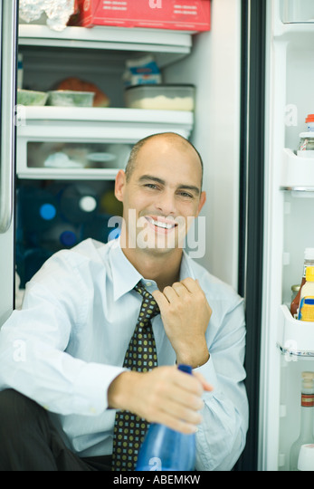 open refrigerator person. man sitting in front of open refrigerator, pulling on collar - stock image refrigerator person i