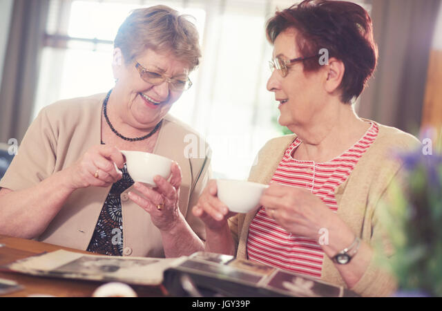 Two senior women laughing while looking at photo album on table - Stock Image