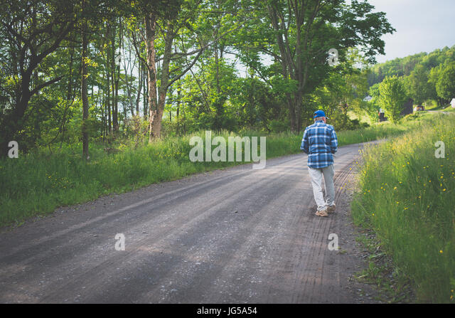 An older man walks alone on a country road. - Stock Image