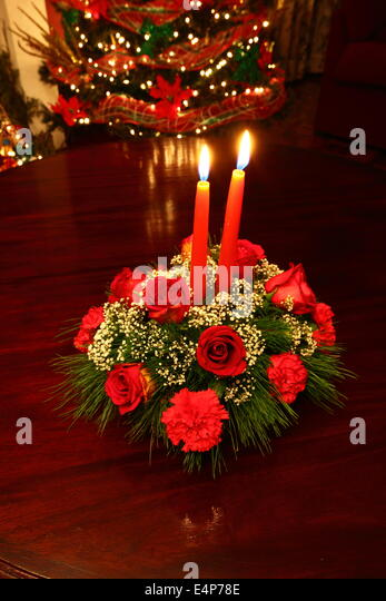 christmas table decoration with red roses carnations and candles christmas tree in background