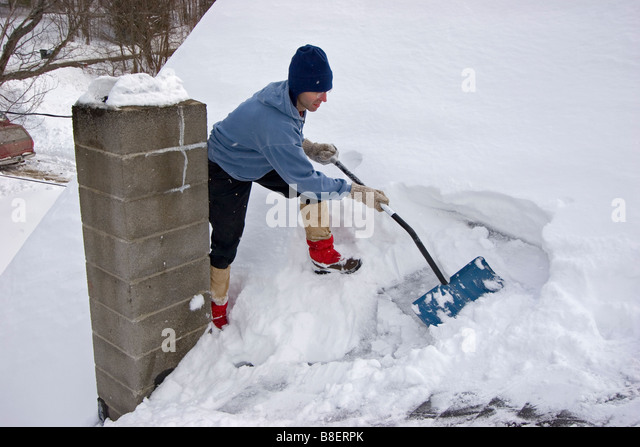 Man On Roof Shoveling Snow In Winter   Stock Image